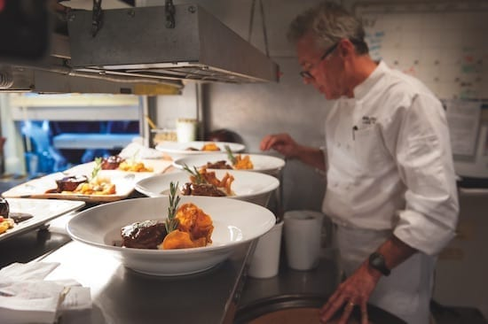 Chef Douglas Dale plating food at Wolfdale's Cuisine Unique