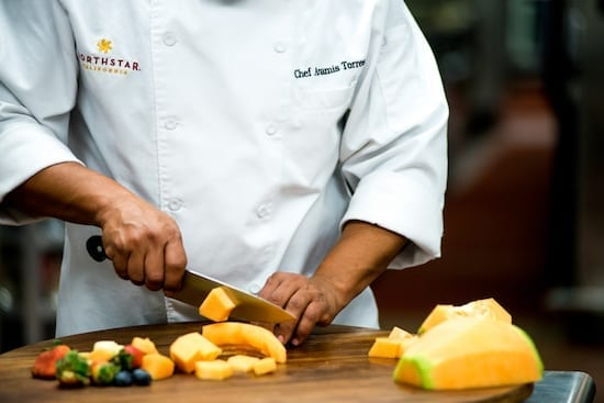 A chef is cutting food at Lake Tahoe Autumn Food & Wine Festival