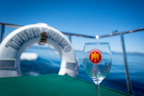 A glass of wine sits atop the historic, Thunderbird Yacht on the waters of North Lake Tahoe