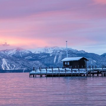 An early evening shot of a snowy Squaw Valley shore with beautiful mountains in the distance and lilac skies.