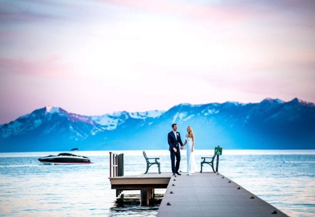 Bride and groom on Lake Tahoe dock with boat in the background