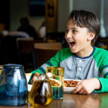 A child dines happily on pizza in a cozy setting.